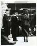 Charles Perry Handing Document to Graduate by Florida International University