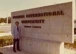Charles Perry Standing Next to the Florida International University Tamiami Campus Nameplate